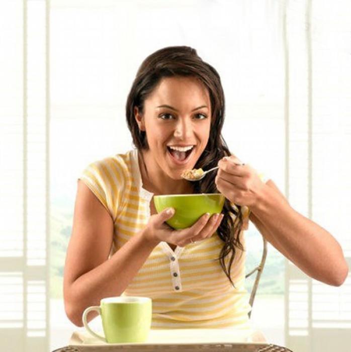 полноценный питательный завтрак девушка с аппетитом ест кашу мюсли с фруктами