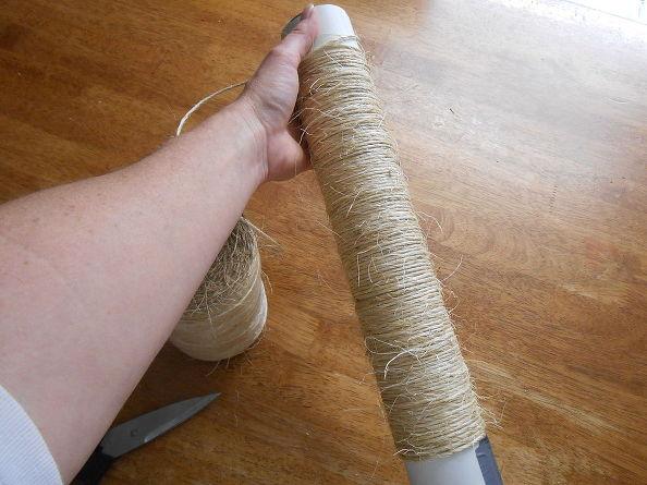 Зафиксировав кончик липкой лентой, на длинную цилиндрическую основу среднего диаметра наматываем натуральную грубую веревку плотными кольцами в большом количестве