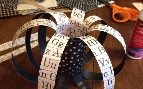 По кругу изнутри рулона вклеиваем верхние кончики полосок из цветной бумаги более нейтрального оттенка сначала сверху, затем снизу