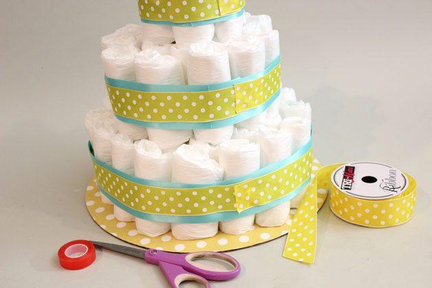 Возьмите менее широкую ленту и точно также оборачиваем ее, но по центру уже закрепленной более широкой ленты на «торте»