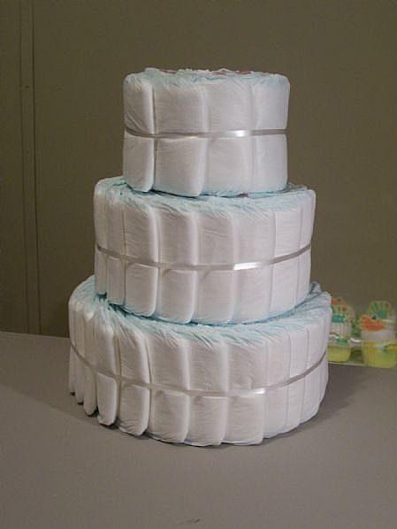 складывать торт можно, не сворачивая подгузники и обойдясь без резинок и бечевки, а просто уложив их немного по диагонали и связав 1 раз лентой