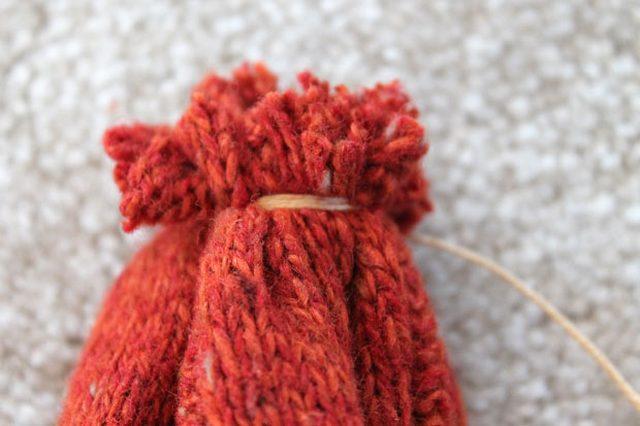 Туго обматываем несколько раз длинный кончик нити вокруг получившегося «пучка» из вязаного материала