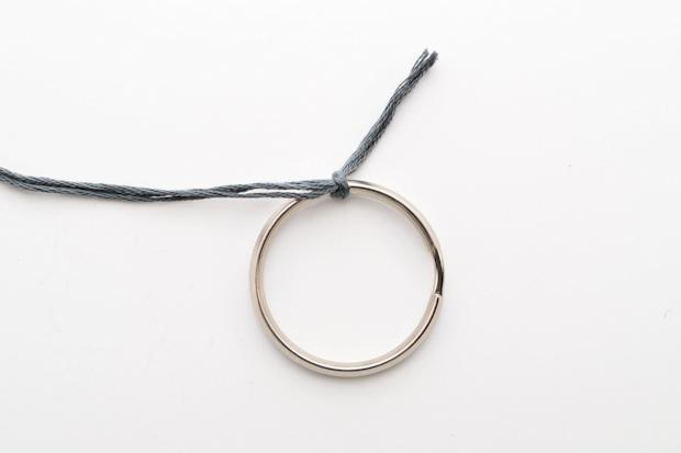 Кончик отрезанного куска мулине туго завяжите вокруг самого крупного кольца