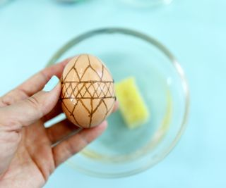 яйцо с восковым рисунком после уксусной ванны и обтирания губкой - фон побледнел