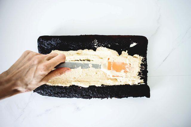 Наполняем полено: когда торт остыл, очень аккуратно его разворачиваем, щедро смачиваем оставшимся Калуа, затем равномерно распределяем по всей основе крем с маскароне