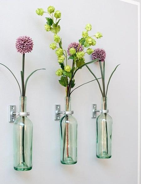 амые обычные белые стеклянные бутылки с высоким горлом, прикрепленные металлическими держателями к стене
