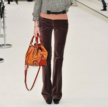 Эти приглушенно-темно-пурпурные брюки смотрятся вечной классикой в сочетании с твидовым топом и ярким всплеском в сумочке.