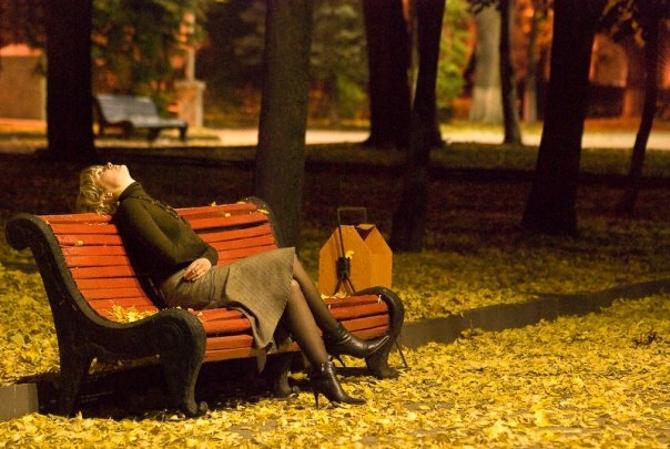 женщина сидит на скамейке грустит