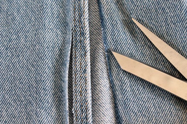 С джинсовой ткани аккуратно срезаем подшитый край