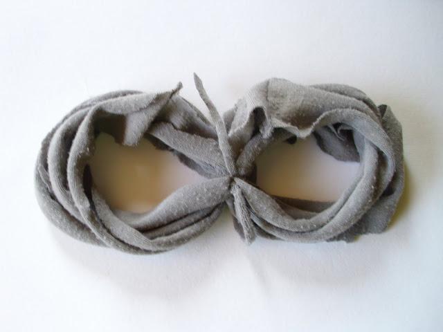 Из оставшейся части футболки нарезаем тонких лент-веревочек и ими связываем наши намотанные кольца попарно