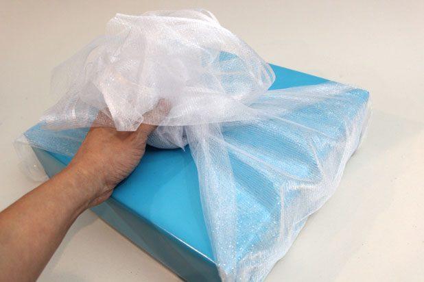 Присберите органзу с двух концов, затем оберните ее по бокам с двух сторон коробки и завяжите сверху на подарке