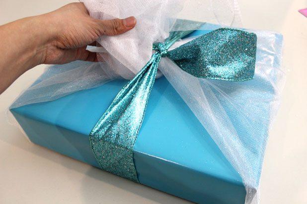 Перпендикулярные бока коробки (перпендикулярно органзе) оберните широкой сверкающей лентой в тон упаковочной бумаге