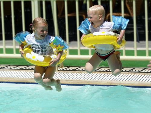 отличный снимок: дети с надувными кругами прыгают в бассейн