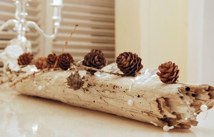 Очищенная светлая коряга, к которой сверху приклеены небольшие шишки с покупной современной декоративной сеточкой между ними - с бусинами под жемчуг на леске