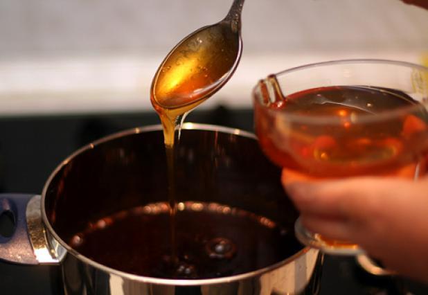 заливает мед в кастрюлю