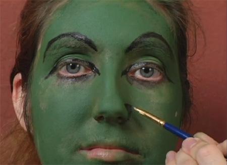 Для классического страшного образа ведьмы полностью покрываем лицо зеленым или серым гримом, выделяем глаза