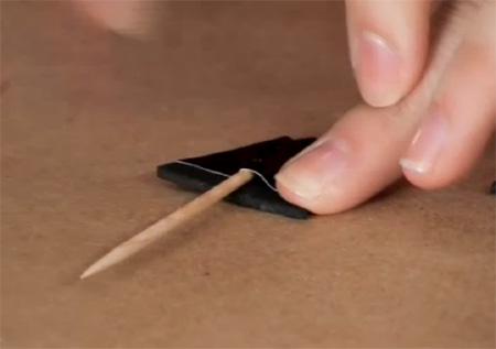 Если вы выбрали какой-то более жесткий аналог пеноматериалу, зубочистки можно прикрепить к задним стенкам ушек при помощи черной липкой ленты