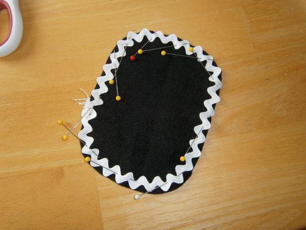 Приколите тесьму зигзагом по всему периметру каждой из овальных черных деталей