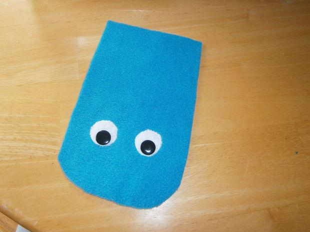 на самую крупную – верхнюю – деталь варежек из яркой ткани на лицевую сторону поместите глаза