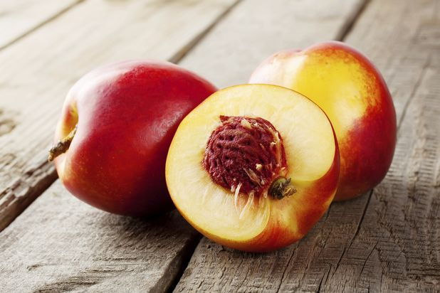 спелые нектарины с разрезанным плодом