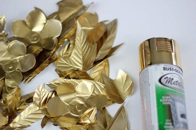 Раскладываем цветы и листья на большом пятачке, выстланном в 3 слоя ненужными газетами, и опрыскиваем все детали венка краской под золото