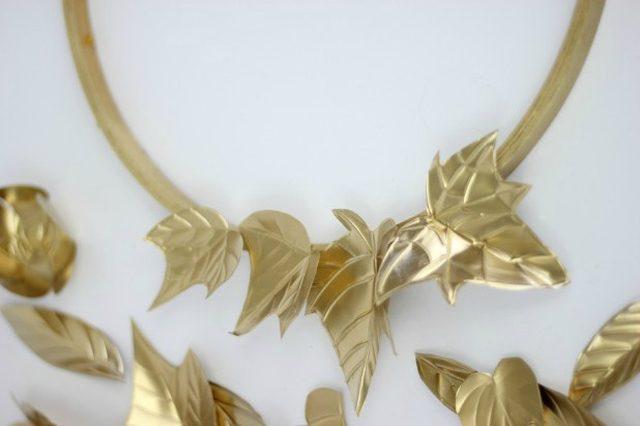 Горячим (или любым другим подходящим) клеем фиксируем детали на круглой основе венка, чередуя малые и большие листья и цветы, кладя их в разных направлениях и в разной степени внахлест