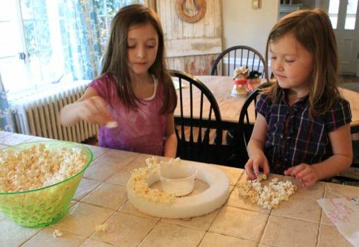 Попкорн (в неготовом виде понадобится около ¾ стакана зерен) наклеивается горячим клеем на поролоновый круг