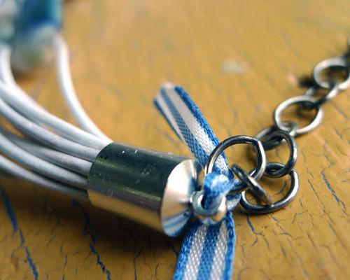 В случае «чашечек» привязываем к петельке на каждой из них по тонкой ленте, связывая крепление с первым звеном своей части цепочки