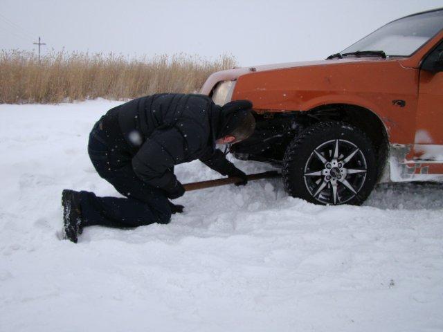 мужик откапывает машину - колеса - лопатой