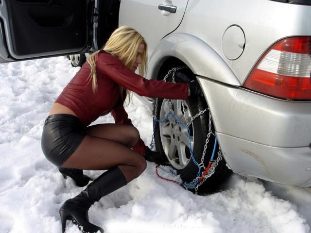 девушка меняет шину зимой