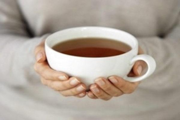 Питье и «удобная» еда в машину зимой: девушка держит в руках горячую чашку чая