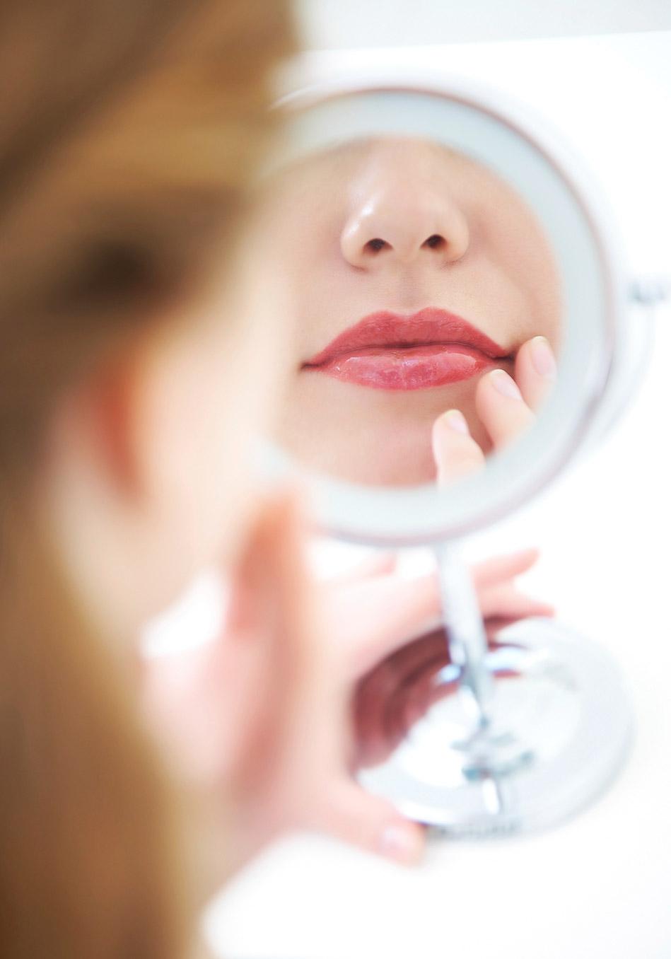 девушка смотрит в настольное зеркало