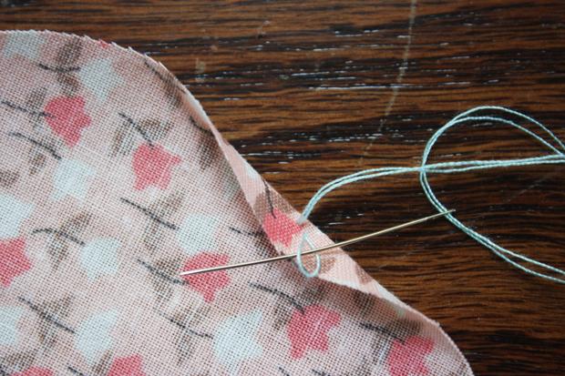 согните край ткани, проденьте нить до маленькой петли