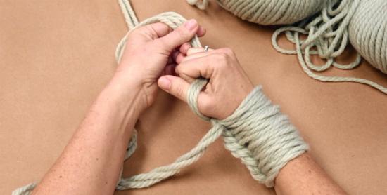 Левой рукой возьмите пряжу, идущую от мотков, и положите ее поверх большого пальца правой руки. Правой рукой схватите пряжу.