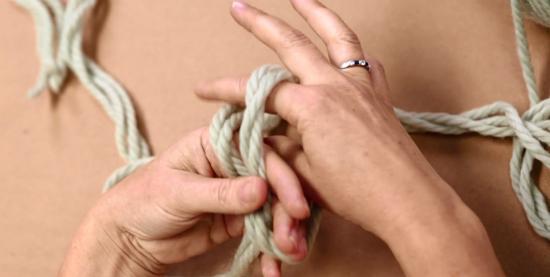 Удерживая большим пальцем левой руки перекрестившиеся кончики пряжи, приснимите получившуюся петлю и с тыльной стороны просуньте в нее верхний кончик пряжи