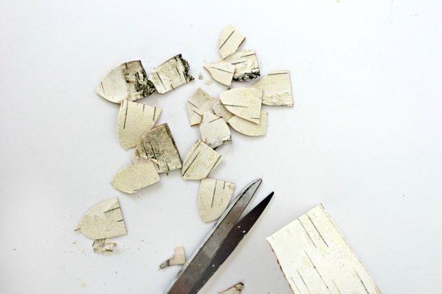 Далее из березовой коры нарезаются «чешуйки шишек», формой похожие на рыцарский шлем