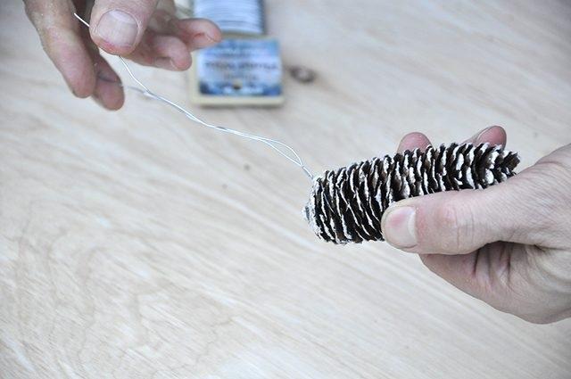 Добавляем в букет немного блеска и гламура, например, окрашенных шишек на ножках из толстой проволоки, которую нужно обернуть вокруг шишки на 2-3 уровне чешуек снизу, а затем туго скрутить кончики, чтобы шишка не выскользнула.