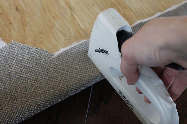 Края ткани вместе с ватином загибаем на фанеру и крепим скобами или очень короткими гвоздями