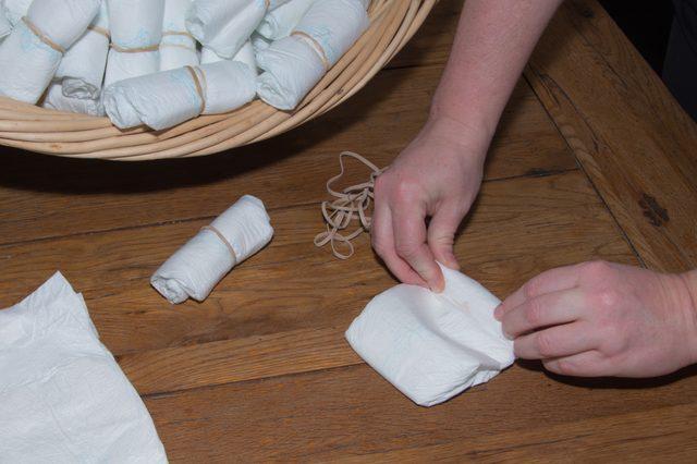 Удерживая вместе края подгузника со стороны его верхней открытой части, начинаем скатывать его в рулончик по направлению к нижней закрытой