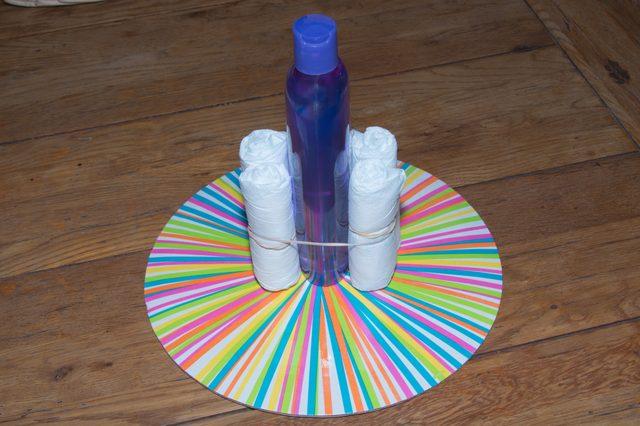 Чтобы выровнять центр основания замка, т. е. сделать центр круглым, вертикально ставим 2 подгузника перед бутылочкой вплотную к ней и 2 точно также сзади бутылки