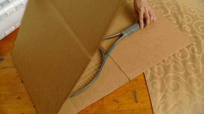 Ракетки кладем в длинный прямоугольник толстого картона, сложенный пополам