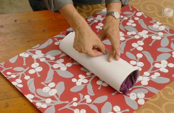 Прозрачной липкой лентой приклеиваем край картона к цилиндру в одном месте