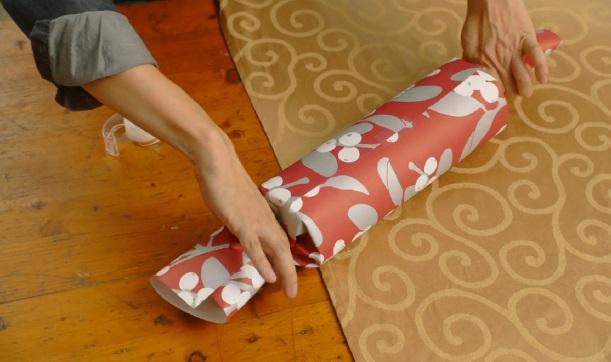 Боковые части бумаги, выходящие за границы цилиндра из картона, сжимаем пальцами, формируя, так сказать, большую конфету