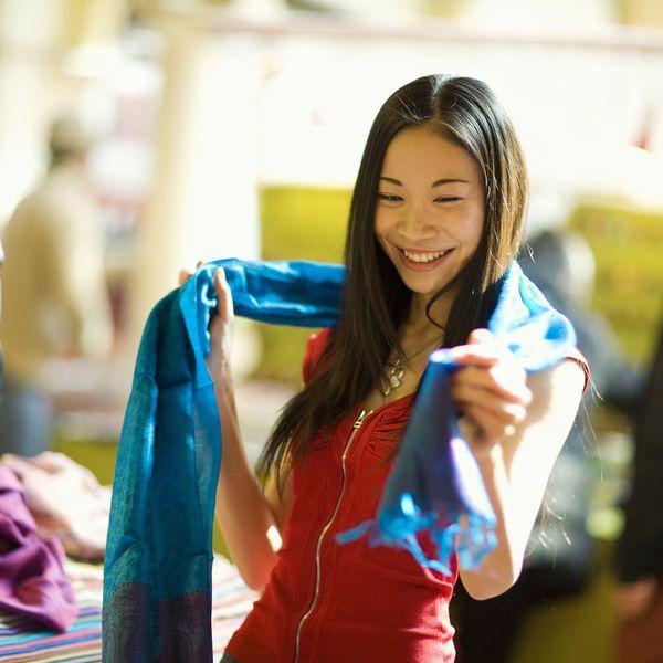 Девушка-азиатка надевает шарф
