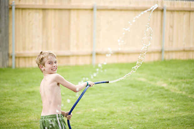 остановить время: вода в полете, мальчик поливает двор из шланга