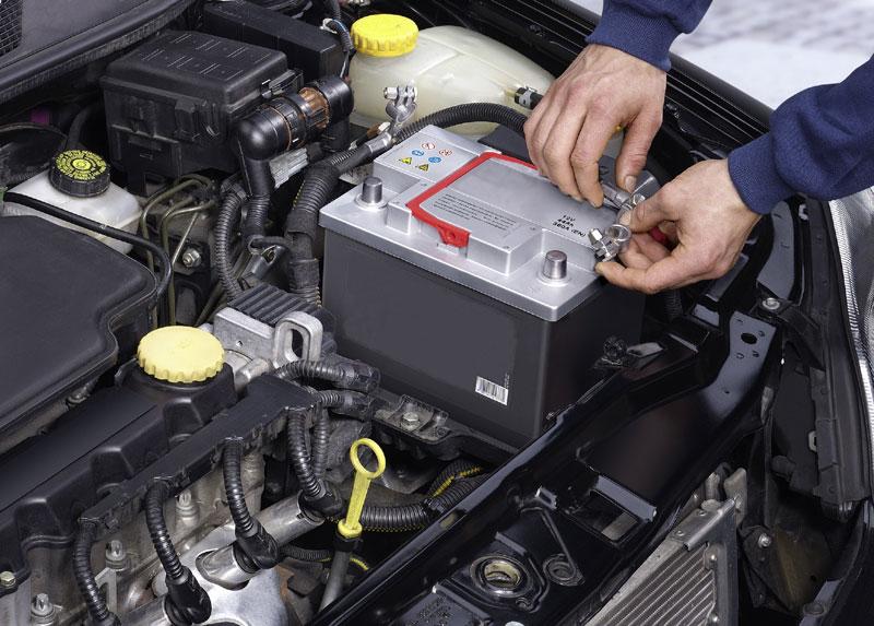 поднятый капот владелец автомобиля снимает аккумулятор