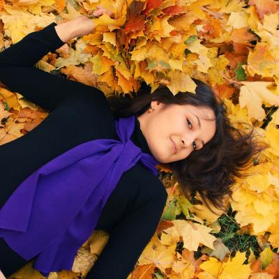 красивая девушка-брюнетка лежит на ярких желтых осенних листьях с букетом кленовых листков