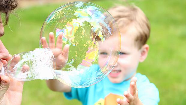 огромный мыльный пузырь из палочки из пластиковой бутылки отец играет с ребенком мальчиком