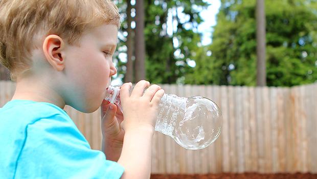 ребенок мальчик выдумает большой мыльный пузырь из пластиковой бутылки
