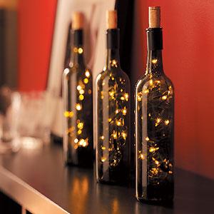 рукодельные бутылки-светильники на каминной полке